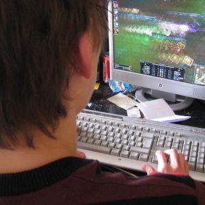 Poika pelaa tietokoneella