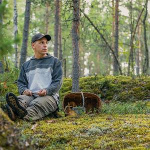 Panu Halme istuu metsässä sienikorin kanssa.