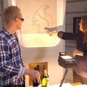 Jim Björni och Camilla Forsén-Ström placerar ut bild av ekorre på vägg.