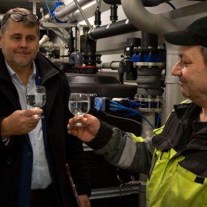Två män ser glada ut och skålar i dricksvatten.