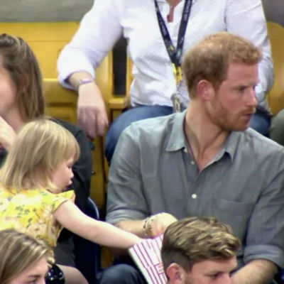 Tvååriga Emily tar popcorn från prins Harrys ask.