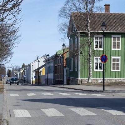 En bild på gamla stan i Brahestad. På bilden syns en väg och några bilar samt ett grönt trähus med vita fönster.