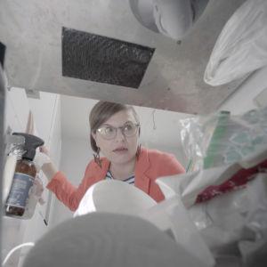 ammattijärjestäjä Ilana Aalto kurkistaa sekaiseen roskiskaappiin