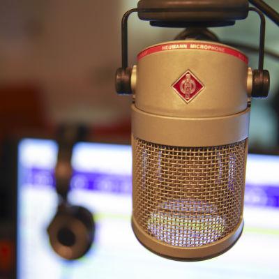 Mikrofoni ja taustalla on kuulokkeet nojaamassa ajolistaan.
