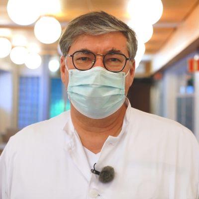 Infektionsöverläkare Asko Järvinen vid Helsingfors och Nylands sjukvårdsdistrikt tittar in i kameran iklädd vit rock och munskydd.