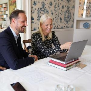 Kronprinsen och kronprinsessan i Norge deltar i videosamtal med en laptop framför sig.