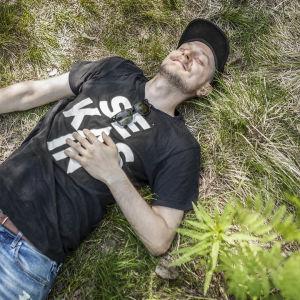 Mikko Toiviainen makaa selällään metsässä ja hymyilee silmät kiinni.