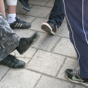 Ungdomar som står i en klunga, man ser deras ben och skor.