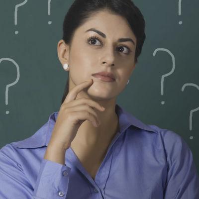 Aristoteleen kantapään artikkelikuva, jossa tummahiuksinen nainen on mietteliäänä ja hänen ynpärillään on kysymysmerkkejä.