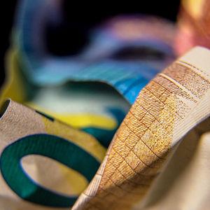 Illustrationsbild på ihopknycklade sedlar.