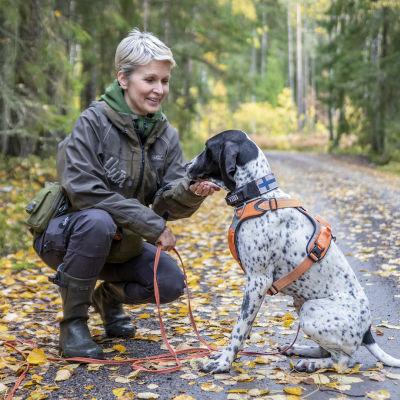 Tanja Karpela on kyykyssä metsätiellä ja hänen vieressään istuu koira.