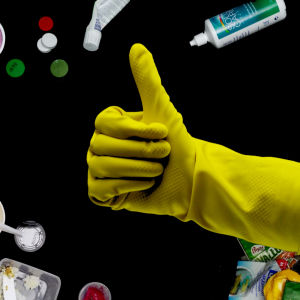 keltainen kumihanska pitää smoothiekuppia ympärillä muoviroskaa