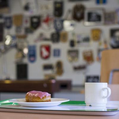 En bricka med en kaffekopp och en munk med ljusröd glasyr.