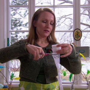 Lee virar en bit spets runt ägget och fäster det med snöre