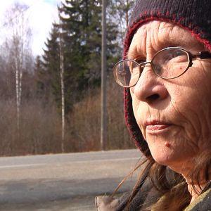 Vanhempi nainen katsoo kaukaisuuteen villamyssy päässä.