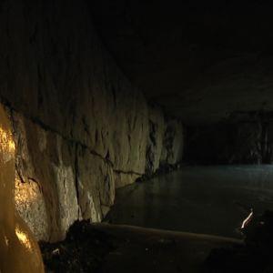 itseräjäytetty luola sisältä, valoa tunnelin päässä