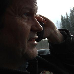 mies puhuu autossa kännykkään