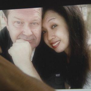 mies katsoo kuvaa rakastuneesta pariskunnasta tietokoneen näytöllä