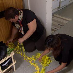 Irma och Elisabeth gör en stig av blomblad.