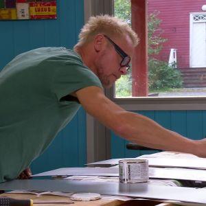 Jim målar plåten vit.