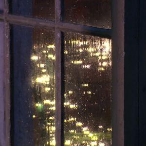 Skenet reflekterar i regnet.
