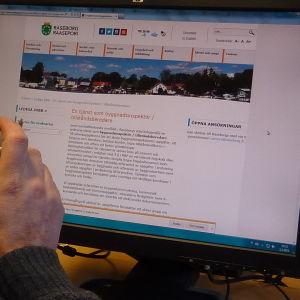 En person som dricker kaffe och tittar på Raseborg stads hemsida.