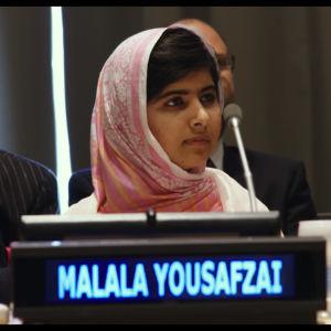 Malala Yousafzai med namnskylten framför sig i samband med en kongress