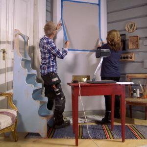 Jim Björni och Camilla Forsén-Ström tar bort målartejp från vägg