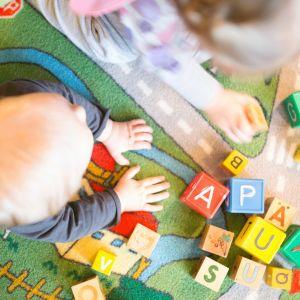 Pienet lapset leikkivät leikkimatolla.