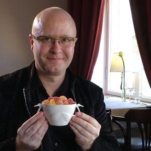 Sami Rinne håller en vit svanskål fylld med marmeladgodis i sina händer.