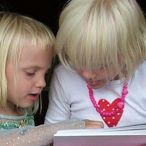Sisarukset lukevat kirjaa.