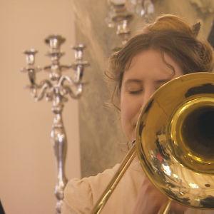 Pasunisti Danna Nelson Kapubändistä eläytyy sadan vuoden takaiseen konserttiin.