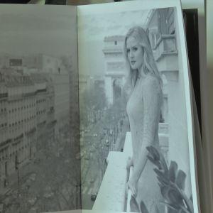 En kvinna i spetsklänning står på en balkong i Paris.
