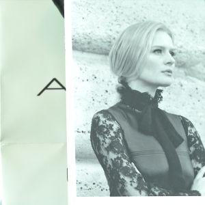 En kvinna i svart spetsskjorta.