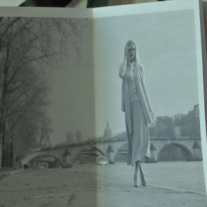 En kvinna i kjol och tröja går vid Seine i Paris.