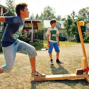 Två pojkar leker med en egenbyggd katapult.