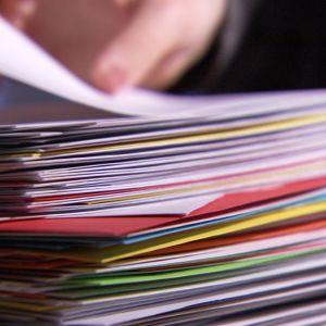 En hand lyfter ett brev ur en hög med många kuvert.