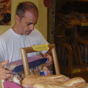 Ranskalaisleipuri Bruno Danizelle järjestelee patonkeja myyntipöydälle.