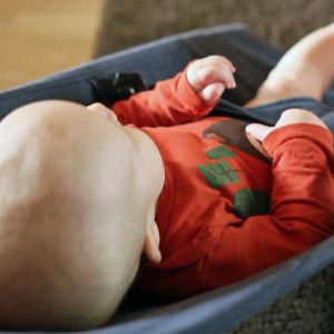 Vauva makaa sitteirssä lattialla.