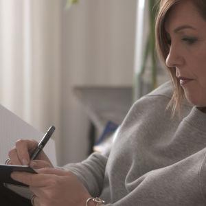 Maria Sundblom Lindberg gör anteckningar i ett häfte.