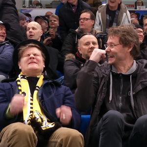 kaksi miestä kokee väkeviä tunteita jääkiekkokatsomossa