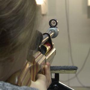 En flicka siktar mot en tavla med luftgevär.