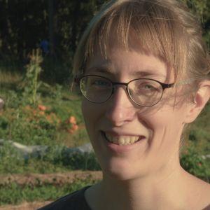 Hymyilevä 30-vuotias nainen katsoo kameraan, taustalla on loppukesän vehreä yhteisöviljelmä, jossa häärii talkoolaisia viljelypuuhissa. Kuvan vasemmassa ylälaidassa on valkoinen logo, jossa kastelukannulla kastellaan kaupunkia. Logossa lukee Syötävä kaupu