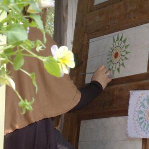 En kvinna målar en mandala på en dörr
