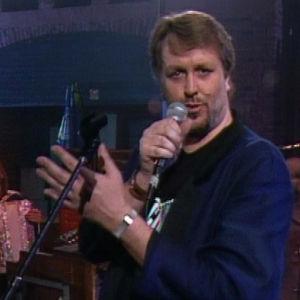 Hector laulaa käsi nostettuna puolittain ylös, taustalla mm. hanuristi Esa Kotilainen.