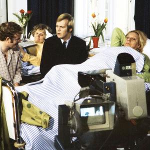 Neil Hardwick henkilöohjaa Ilmari Saarelaista ja Sylvi Salosta sairaalakohtauksessa tv-kameran edessä. Taustalla Anja Räsänen.