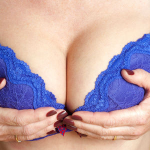 en kvinna i bh som stöder sina bröst med sina båda händer