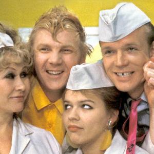 Eeva Litmanen, Kari Heiskanen, Ilkka Heiskanen ja Kati Bergman valintamyymälän uniformuissaan Mutapainin ystävät -sarjassa