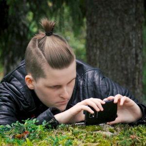 Hanna Bäckström fotograferar med sin mobil ute i skogen.