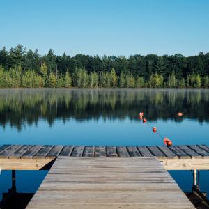 Mindfulness-vinkeillä irti kesästä juuri sinulle itsellesi hyvää. Kuvassa laituri ja metsälampi.